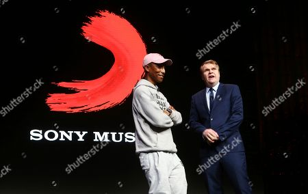 Rob Stringer, right, CEO of Sony Music Entertainment, surprises the audience as musician Pharrell Williams, left, walks on stage at the Sony news conference at CES International, in Las Vegas