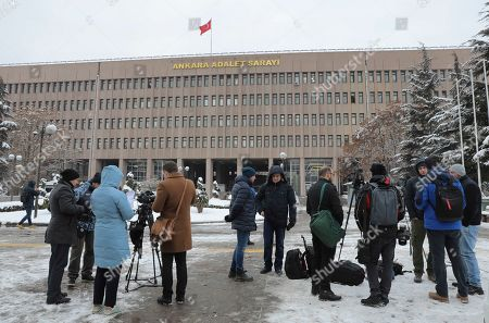 Members of the media work outside a court in Ankara, Turkey, where a trial has opened against 28 people accused of involvement in the 2016 killing of Russia's ambassador to Turkey. An off-duty police officer fatally shot Andrei Karlov at a photo exhibition in Ankara on Dec. 19, 2016. The officer was later shot dead at the scene by police