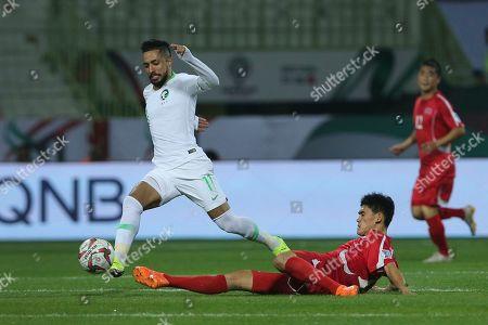 Saudi Arabia's midfielder Hattan Bahebri, left, moves past North Korea's midfielder Ri Un-Chol during the AFC Asian Cup group E soccer match between Saudi Arabia and North Korea at the Rashid Stadium in Dubai, United Arab Emirates