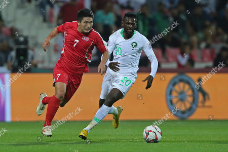 North Korea's forward Han Kwang Song, left, tussles for the ball with Saudi Arabia's midfielder Abdulaziz Al-Bishi during the AFC Asian Cup group E soccer match between Saudi Arabia and North Korea at the Rashid Stadium in Dubai, United Arab Emirates
