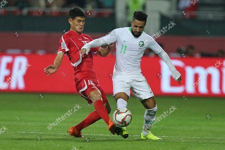 Saudi Arabia's midfielder Hattan Bahebri, right, tussles for the ball with North Korea's midfielder Ri Un-Chol during the AFC Asian Cup group E soccer match between Saudi Arabia and North Korea at the Rashid Stadium in Dubai, United Arab Emirates