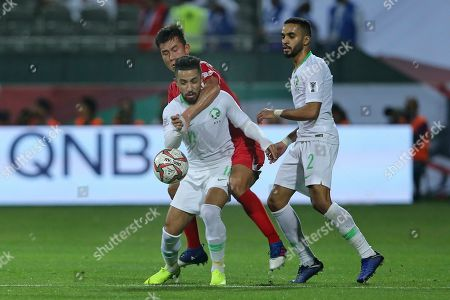 Saudi Arabia's midfielder Hattan Bahebri, front, tussles for the ball with North Korea's defender Kim Chol-Bom, background, during the AFC Asian Cup group E soccer match between Saudi Arabia and North Korea at the Rashid Stadium in Dubai, United Arab Emirates
