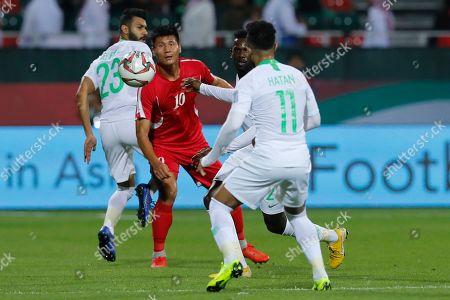 North Korea's forward Pac Kwang-Ryong, centre, is blocked by Saudi Arabia's defender Mohammed Al-Fatil, left, and Saudi Arabia's midfielder Hattan Bahebri during the AFC Asian Cup group E soccer match between Saudi Arabia and North Korea at the Rashid Stadium in Dubai, United Arab Emirates