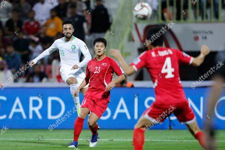 Saudi Arabia's midfielder Hattan Bahebri, kicks past North Korea's defender Ri Il-Jinand North Korea's defender Kim Song-Gi during the AFC Asian Cup group E soccer match between Saudi Arabia and North Korea at the Rashid Stadium in Dubai, United Arab Emirates
