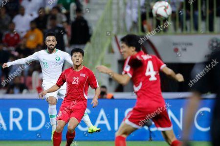 Saudi Arabia's midfielder Hattan Bahebri, scores the first goal past North Korea's defender Ri Il-Jinand North Korea's defender Kim Song-Gi during the AFC Asian Cup group E soccer match between Saudi Arabia and North Korea at the Rashid Stadium in Dubai, United Arab Emirates