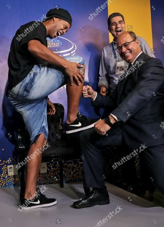 Brazilian former soccer player Ronaldinho Gaucho (L) puts his feet on the knee of Rio de Janeiro Governor Wilson Witzel (R) after leaving his footprints for the Maracana Stadium's sidewalk of the fame, in Rio de Janeiro, Brazil, 08 January 2018. Others are not identified.
