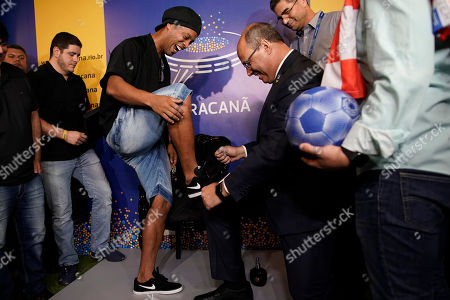 Rio de Janeiro Gov. Wilson Witzel, right, pretends to clean the shoe of Brazil's former soccer player Ronaldinho Gaucho, before Ronaldinho prints his feet on a plaque for Brazil's Soccer Walk of Fame at Maracana stadium in Rio de Janeiro, Brazil, . Ronaldinho was twice named FIFA World Player of the Year