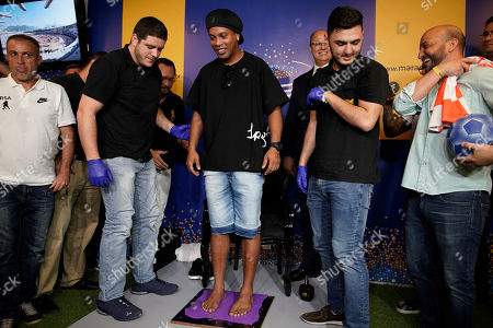 Brazil's former soccer player Ronaldinho Gaucho places stands on molding material to make a plaque of his footprints for Brazil's Soccer Walk of Fame at Maracana stadium in Rio de Janeiro, Brazil, . Ronaldinho was twice named FIFA World Player of the Year