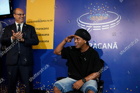 Brazil's former soccer player Ronaldinho Gaucho greets fans with a salute as Rio de Janeiro Gov. Wilson Witzel applauds before printing his feet for a plaque to be placed on Brazil's Soccer Walk of Fame at Maracana stadium in Rio de Janeiro, Brazil, . Ronaldinho was twice named FIFA World Player of the Year