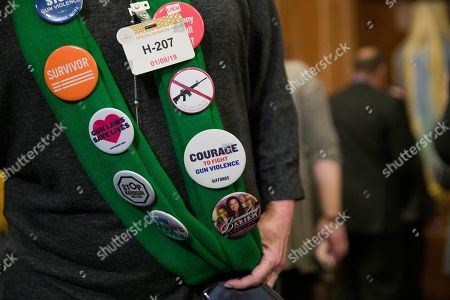 Sandy Phillips, whose daughter Jessi Ghawi was killed in the Aurora, Colo., movie theater shooting, wears a collection of buttons on her daughter's scarf before a news conference to announce the introduction of bipartisan legislation to expand background checks for sales and transfers of firearms, on Capitol Hill, in Washington