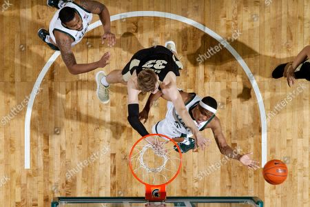 Michigan State's Cassius Winston, right, shoots against Purdue's Matt Haarms, center, as Michigan State's Nick Ward, left, watches during the first half of an NCAA college basketball game, in East Lansing, Mich. Michigan State won 77-59