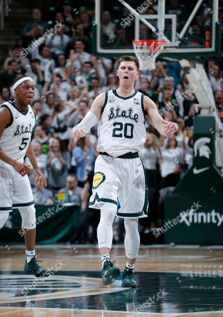 Michigan State's Matt McQuaid (20) and Cassius Winston celebrate during the first half of an NCAA college basketball game against Purdue, in East Lansing, Mich. Michigan State won 77-59