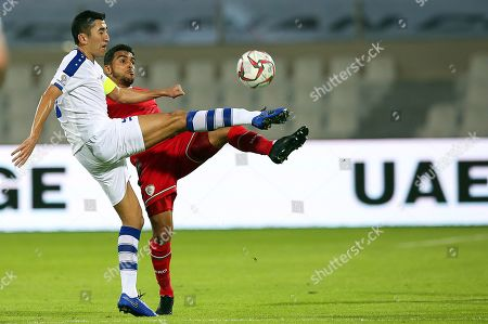 Stock Photo of Odil Ahmedov (L) of Uzbekistan in action against Mohammed Al Musallami (R) of Oman during the 2019 AFC Asian Cup group F preliminary round match between Uzbekistan and Oman in Sharjah, United Arab Emirates, 09 January 2019.