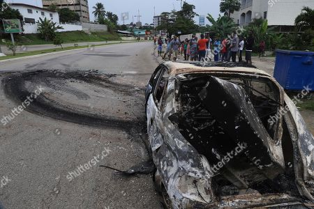 "People stand by a burnt out car on the street after a failed coup attempt in Libreville, Gabon. Gabon's ruling party says ailing President Ali Bongo Ondimba will return to the country ""very soon"" after a coup attempt early this week. The Gabonese Democratic Party secretary-general spoke after authorities inspected the bloody scene where soldiers briefly took over the state radio station on Monday"