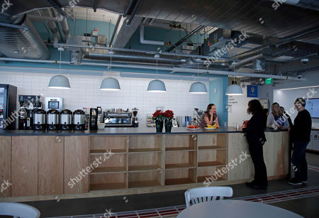 People gather at a food bar at Facebook's new 130,000-square-foot offices, which occupy the top three floors of a 10-story Cambridge, Mass. building. The space gives the company room to triple its current local staff of more than 200. The Silicon Valley company, created by Mark Zuckerberg when he was two subway stops away at Harvard University, opened its first Boston office five years ago