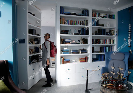 """Stock Image of Educator Angela Allen opens a """"secret room"""" during a tour for media and guests of Facebook's new 130,000-square-foot offices, which occupy the top three floors of a 10-story Cambridge, Mass. The space gives the company room to triple its current local staff of more than 200. The Silicon Valley company, created by Mark Zuckerberg when he was two subway stops away at Harvard University, opened its first Boston office five years ago"""
