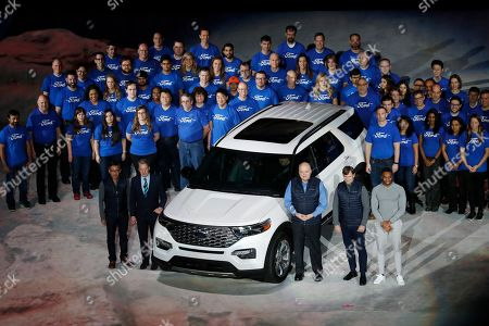 From left, Ford Motor Co., executives Hau Thai-Tang, Bill Ford, Jim Hackett and Jim Farly with team members stand next to the redesigned 2020 Ford Explorer during its unveiling, in Detroit. Ford's aging Explorer SUV is getting a major revamp as it faces growing competition in the market for family haulers with three rows of seats. The Explorer gets a top-to-bottom update that includes a switch from front- to rear-wheel-drive, as well as upgraded engines and transmissions
