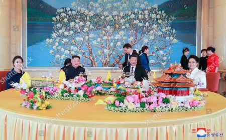 "Provided on Jan. 10, 2019, by the North Korean government, North Korean leader Kim Jong Un, center left, and his wife Ri Sol Ju, left, and Chinese President Xi Jinping, center right, and his wife Peng Liyuan, right in front, attend a luncheon at the Beijing Hotel in Beijing. The content of this image is as provided and cannot be independently verified. Korean language watermark on image as provided by source reads: ""KCNA"" which is the abbreviation for Korean Central News Agency"