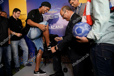 Rio de Janeiro Gov. Wilson Witzel, right, pretends to clean the shoe of Brazil's former soccer player Ronaldinho Gaucho, after Ronaldinho printed his feet on a plaque for Brazil's Soccer Walk of Fame at Maracana stadium in Rio de Janeiro, Brazil. Ronaldinho was twice named FIFA World Player of the Year