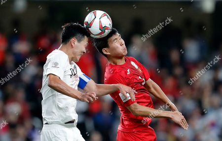 South Korea's defender Kim Young-Gwon jumps for the ball with Kyrgyz Republic's defender Tamirlan Kozubaev, right, during the AFC Asian Cup group C soccer match between Kyrgyzstan and South Korea at Hazza Bin Zayed Stadium in Al Ain, United Arab Emirates