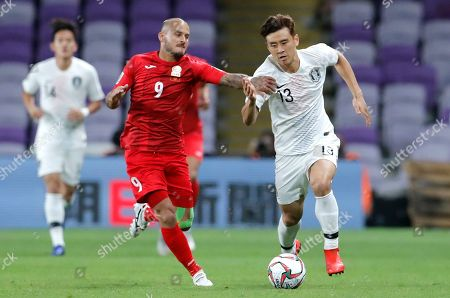 Kyrgyz Republic's midfielder Edgar Bernhardt vies for the ball with South Korea's midfielder Koo Ja-Cheol, right, during the AFC Asian Cup group C soccer match between Kyrgyzstan and South Korea at Hazza Bin Zayed Stadium in Al Ain, United Arab Emirates