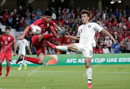 Kyrgyz Republic's defender Tamirlan Kozubaev fights for the ball with South Korea's midfielder Koo Ja-Cheol, right, during the AFC Asian Cup group C soccer match between Kyrgyzstan and South Korea at Hazza Bin Zayed Stadium in Al Ain, United Arab Emirates