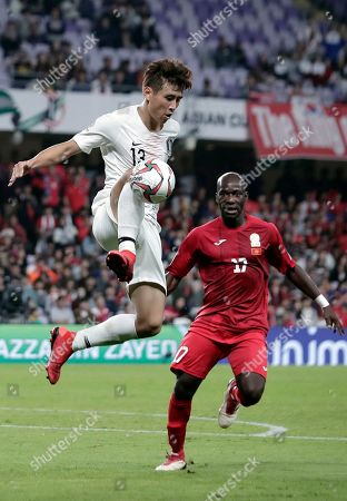South Korea's midfielder Koo Ja-Cheol, left, controls the ball in front of Kyrgyz Republic's defender Daniel Tagoe during the AFC Asian Cup group C soccer match between Kyrgyzstan and South Korea at Hazza Bin Zayed Stadium in Al Ain, United Arab Emirates