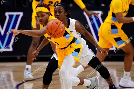 Marquette's Danielle King, left, eyes the ball against Villanova's Raven James, center, during the fourth quarter of an NCAA college basketball game, in Bryn Mawr, Pa. Marquette won 91-55