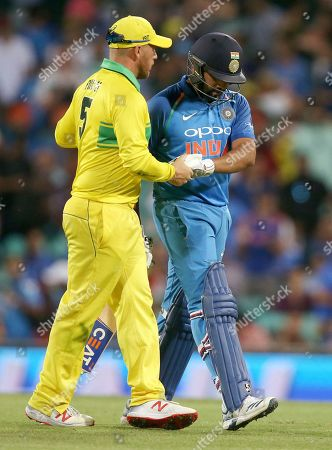 Australia's Aaron Finch, left, shakes hands with India's Rohit Sharma, right, after he was caught out against during their one day international cricket match in Sydney