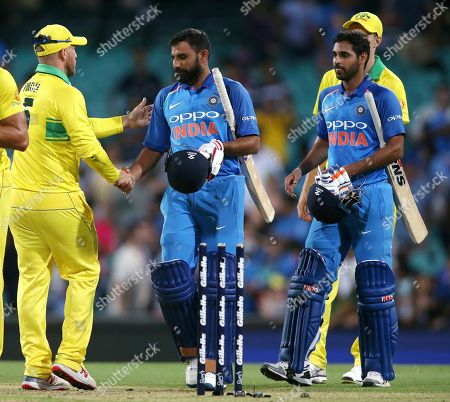 Australia's captain Aaron Finch, left, shakes hands with India's Mohammed Shami, center, and Bhuvneshwar Kumar, right, at the end of their one day international cricket match in Sydney