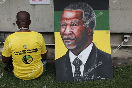 An ANC (African National Congress) supporter sits next to a painting of former ANC South African President Thabo Mbeki during the ANC Election manifesto launch, Durban, South Africa, 12 January 2019. The ANC (African National Congress) have been the ruling party since the end of the minority white rule of the Apartheid system in 1994. The elections will be the countries 5th as the ANC lose voters after corruption allegations, lack of service delivery and the advent of other opposition parties. General elections will be in May with the date still to be announced.