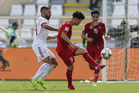 Stock Photo of Vietnam's forward Nguyen Song Phuong, center, controls the ball past Iran's defender Rouzbeh Cheshmi during the AFC Asian Cup group D soccer match between Iran and Vietnam at Al Nahyan Stadium in Abu Dhabi, United Arab Emirates