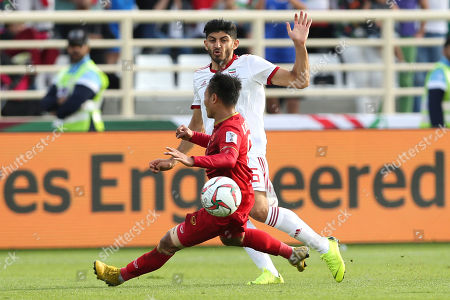 Iran's midfielder Mehdi Torabi, background, plays the ball past Vietnam's midfielder Nguyen Trong hoang during the AFC Asian Cup group D soccer match between Iran and Vietnam at Al Nahyan Stadium in Abu Dhabi, United Arab Emirates