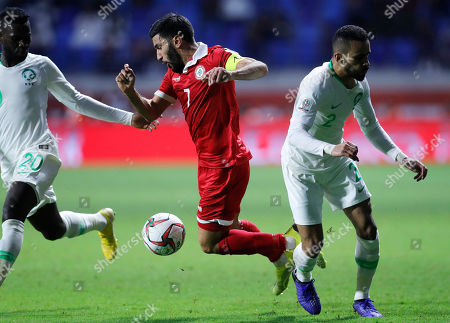Lebanon's forward Hassan Maatouk, center, fights for the ball with Saudi Arabia players midfielder Abdulaziz Al-Bishi, left, and Mohammed Al-Burayk, right, during the AFC Asian Cup group E soccer match between Lebanon and Saudi Arabia at Al Maktoum Stadium in Dubai, United Arab Emirates