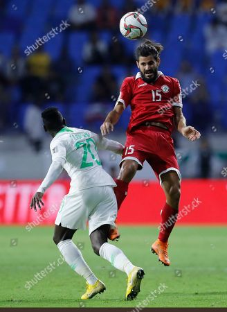 Lebanon's midfielder Haytham Faour, right, jumps to head the ball against Saudi Arabia's midfielder Abdulaziz Al-Bishi, left, during the AFC Asian Cup group E soccer match between Lebanon and Saudi Arabia at Al Maktoum Stadium in Dubai, United Arab Emirates