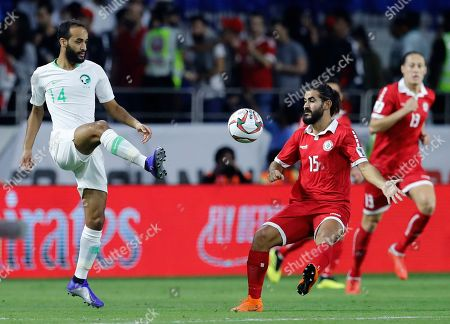 Saudi Arabia's midfielder Abdullah Otayf, left, fights for the ball with Lebanon's midfielder Haytham Faour, right, during the AFC Asian Cup group E soccer match between Lebanon and Saudi Arabia at Al Maktoum Stadium in Dubai, United Arab Emirates