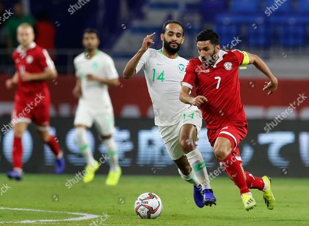 Stock Image of Lebanon's forward Hassan Maatouk, right, fights for the ball with Saudi Arabia's midfielder Abdullah Otayf, center, during the AFC Asian Cup group E soccer match between Lebanon and Saudi Arabia at Al Maktoum Stadium in Dubai, United Arab Emirates