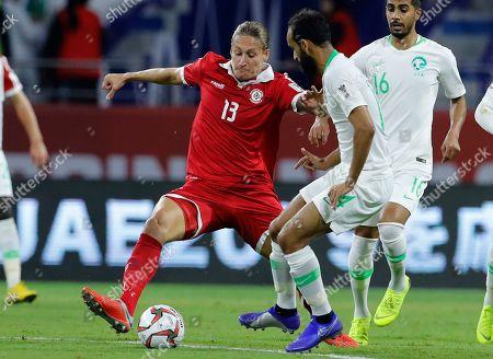 Lebanon's defender Felix Michel, left, fights for the ball with Saudi Arabia's midfielder Abdullah Otayf, right, during the AFC Asian Cup group E soccer match between Lebanon and Saudi Arabia at Al Maktoum Stadium in Dubai, United Arab Emirates