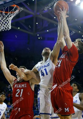 Buffalo center Brock Bertram (41) fights for a rebound against Miami of Ohio forward Aleks Abrams (21) and forward Michael Ritchie (25) during the second half of an NCAA college basketball game, in Buffalo N.Y