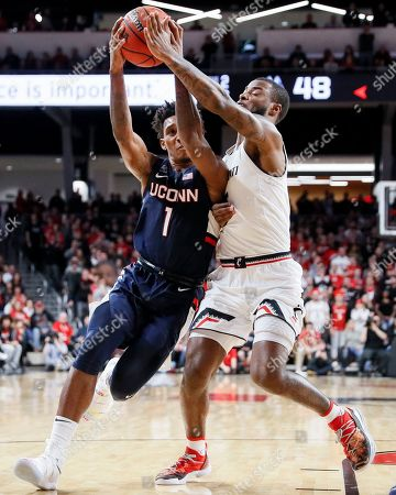 Christian Vital, Trevor Moore. Connecticut's Christian Vital (1) drives against Cincinnati's Trevor Moore (5) in the second half of an NCAA college basketball game, in Cincinnati