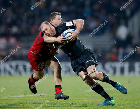 Schalk Burger of Saracens is tackled by Deon Fourie of Lyon