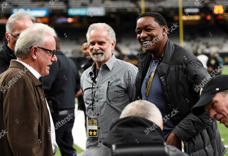 Former Detroit Pistons basketball player Isiah Thomas, right, talks on the sideline before an NFL divisional playoff football game between the New Orleans Saints and the Philadelphia Eagles in New Orleans