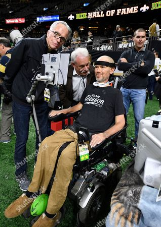 Stock Image of Former New Orleans Saints player Steve Gleason, who suffers from amyotrophic lateral sclerosis (ALS), looks at his screen with former Saints assistant coach Joe Vitt, center, before an NFL divisional playoff football game against the Philadelphia Eagles, in New Orleans