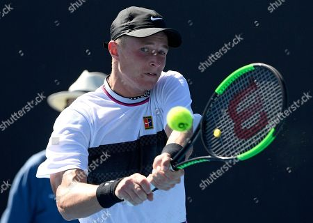 Germany's Rudolf Molleker makes a backhand return to Argentina's Diego Schwartzman during their first round match at the Australian Open tennis championships in Melbourne, Australia