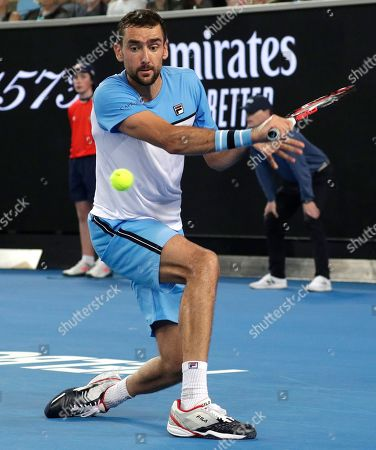 Croatia's Marin Cilic makes a backhand return to Australia's Bernard Tomic during their first round match at the Australian Open tennis championships in Melbourne, Australia