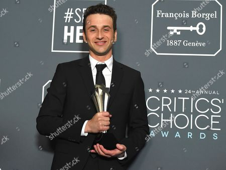 """Stock Picture of Justin Hurwitz poses in the press room with the award for best score for """"First Man"""" at the 24th annual Critics' Choice Awards, at the Barker Hangar in Santa Monica, Calif"""