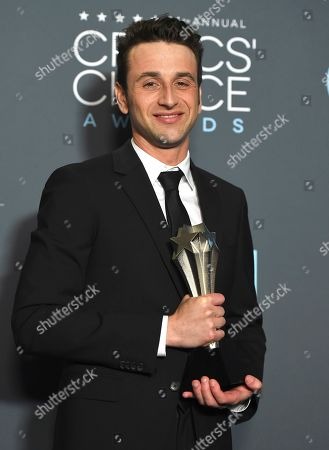 """Stock Image of Justin Hurwitz poses in the press room with the award for best score for """"First Man"""" at the 24th annual Critics' Choice Awards, at the Barker Hangar in Santa Monica, Calif"""