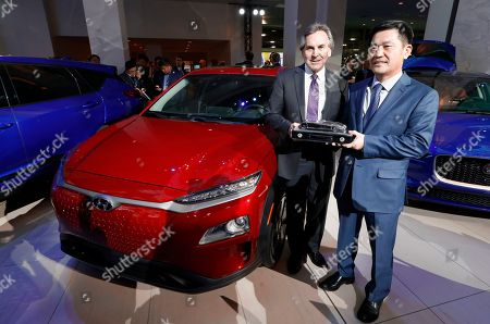 Brian Smith, left, Chief Operating Officer, Hyundai Motor America and Yong-woo William Lee, President and CEO of Hyundai Motor North America hold the North American SUV of the Year trophy next to the Hyundai Kona award during media previews for the North American International Auto Show in Detroit