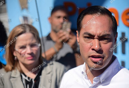 Julian Castro speaks to the press in Playita, one of the poorest and most affected communities by Hurricane Maria, as San Juan Mayor Carmen Yulin Cruz Soto stands behind him in San Juan, Puerto Rico, . The presidential candidate has joined dozens of high-profile Latinos in Puerto Rico to talk about mobilizing voters ahead of the 2020 elections and increasing Latino political representation to take on President Donald Trump