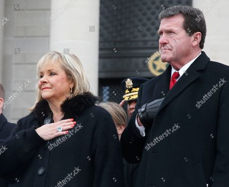 Stock Picture of Former Oklahoma Governor Mary Fallin, left, and her husband, Wade Christensen, right, hold their hands over their hearts during the playing of the national anthem during inaugural ceremonies for Oklahoma Governor Kevin Stitt in Oklahoma City